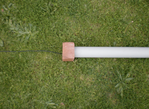 A standard pipe is set up on the backyard lawn with a brick placed at either end, a small gap is made between the brick and the pipe to allow the air to pass through.  A stereo condensor microphone is positioned in the middle of the pipe.